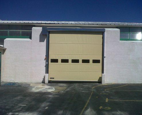 Standardowa brama przemysłowa WinRoll 150 w kolorze piaskowym na zewnątrz budynku.