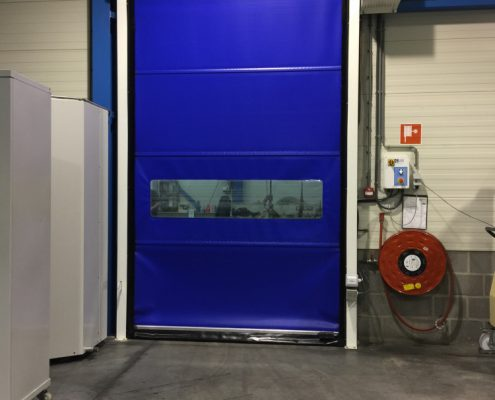 Niebieska brama przemysłowa rolowana WinRoll 150 w obiekcie magazynowym o małej powierzchni.