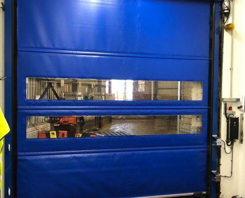 Niebieska brama przemysłowa rolowana WinRoll 150 w obiekcie handlowo-usługowym.