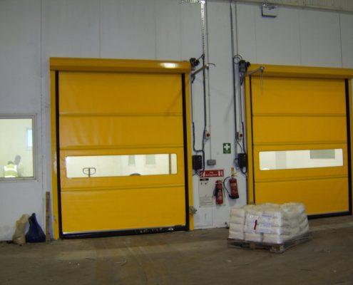 Żółte bramy przemysłowe, rolowane WinRoll 150 w obiekcie magazynowym.