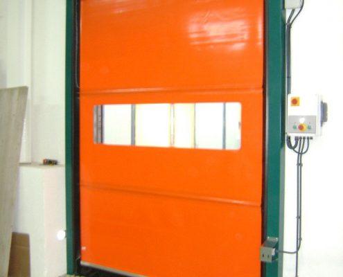 Pomarańczowa brama przemysłowa rolowana WinRoll 150 w obiekcie magazynowym.